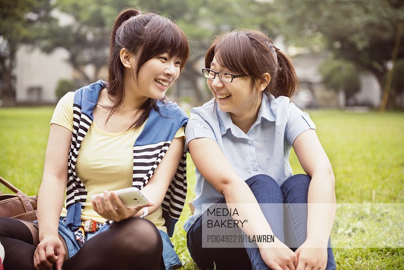 Two girls chatting on grassland