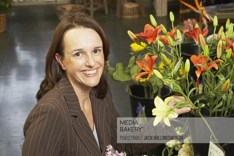 Portrait of a businesswoman holding a flower in a flower shop