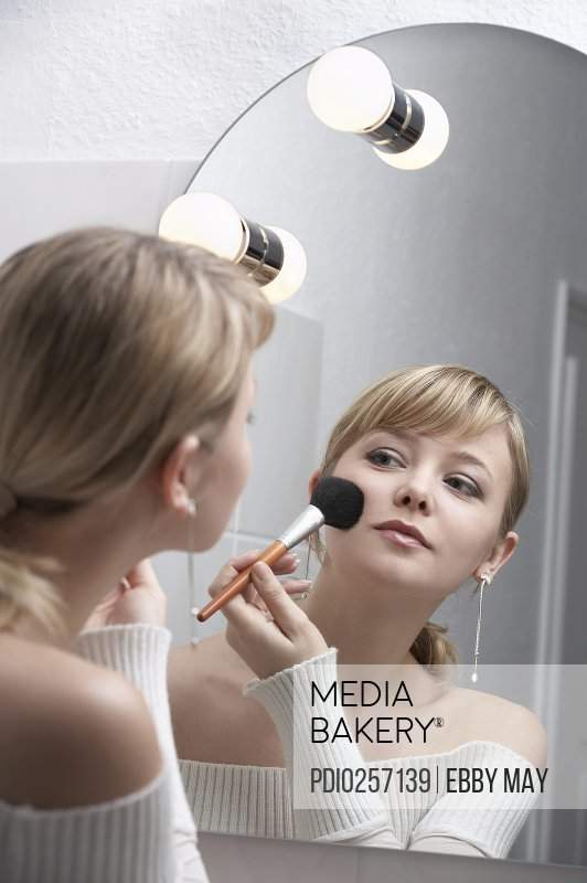Young woman applying make-up in mirror (focus on reflection)