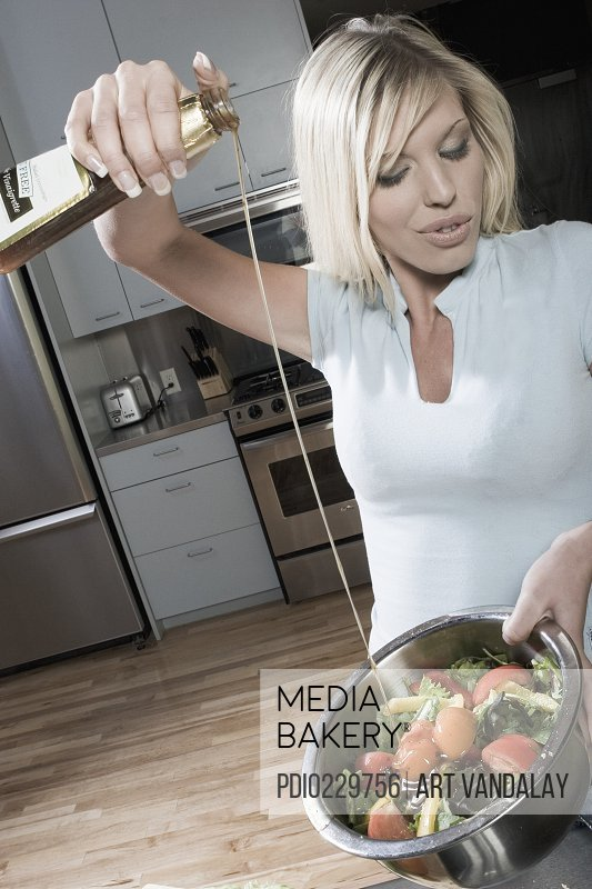 Young woman pouring salad dressing onto salad in domestic kitchen
