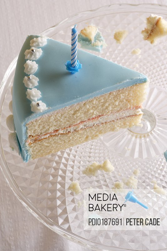 Birthday cake slice on glass serving dish