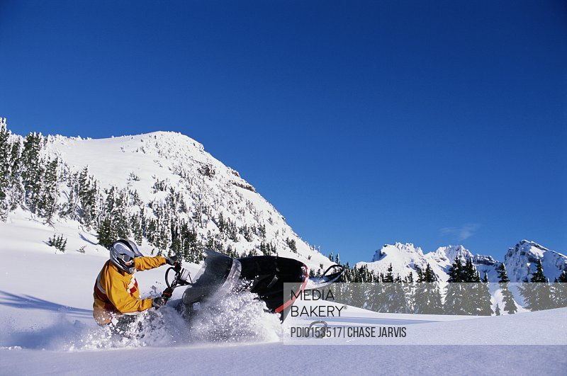 Man on snowmobile cutting through snow
