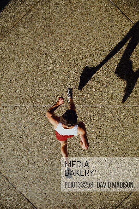 Man jogging on sidewalk (overhead view)