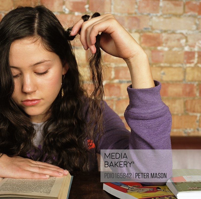 Teenage girl (15-17) reading while twirling her hair