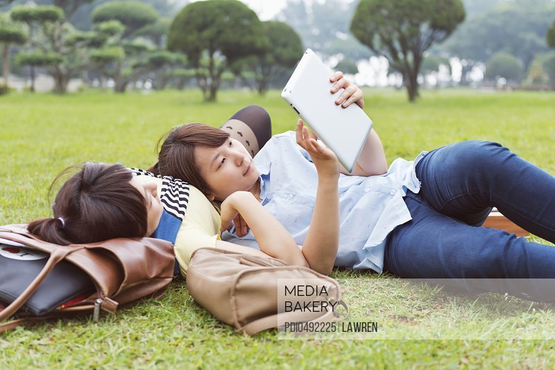 Two girls looking at tablet on grassland