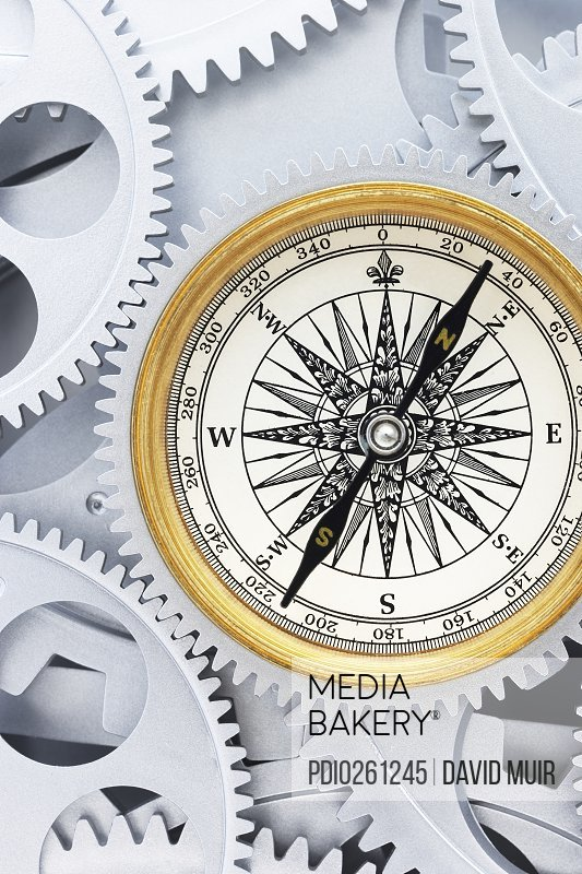 Compass rose against cog and gear wheels