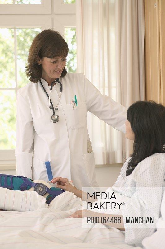 Mature female doctor visiting female patient