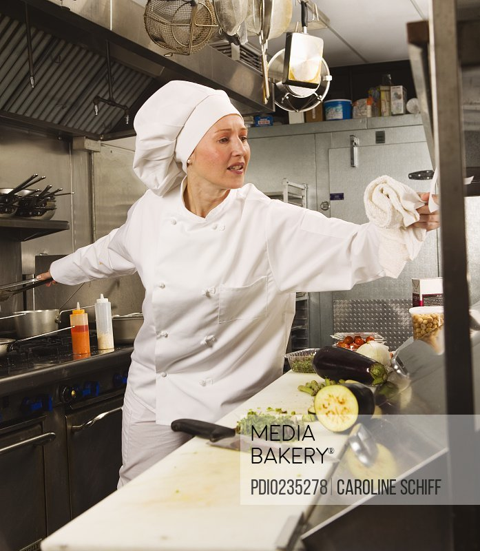 Female chef preparing food in commercial kitchen