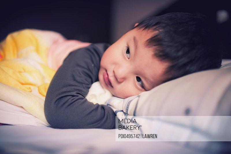 Little child lies on bed/n
