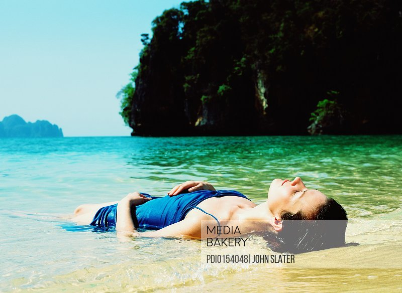 Young woman lying in surf