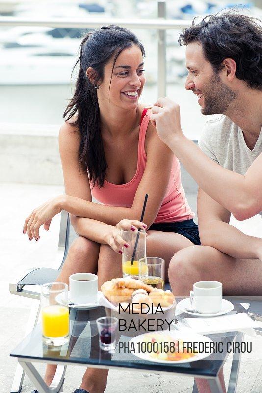 Boyfriend feeding girlfriend breakfast outdoors