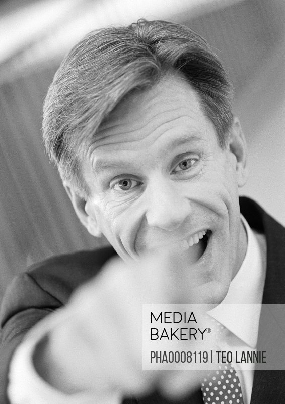Businessman pointing at camera, hand blurred in foreground, black and white, close-up, portrait.