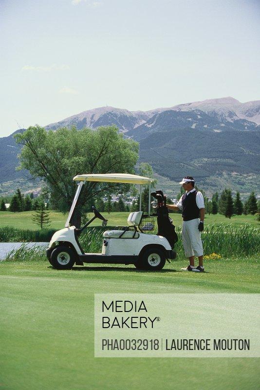 Golfer taking golf bag from golf cart