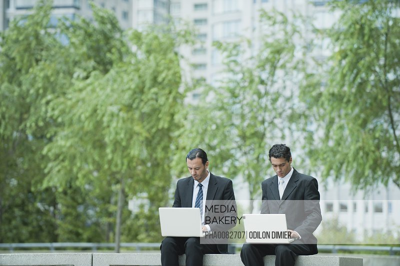 Businessmen sitting side by side using laptop computers outdoors