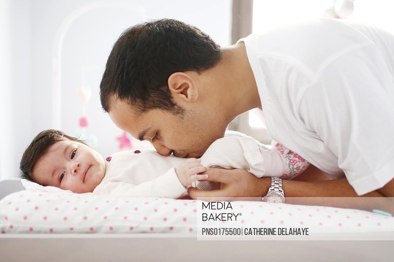 A 2 months old baby girl on a changing table, her dad taking care of
