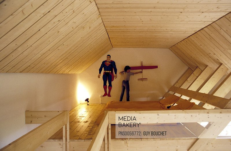 Boy holding a plane in its wooden room under the roof