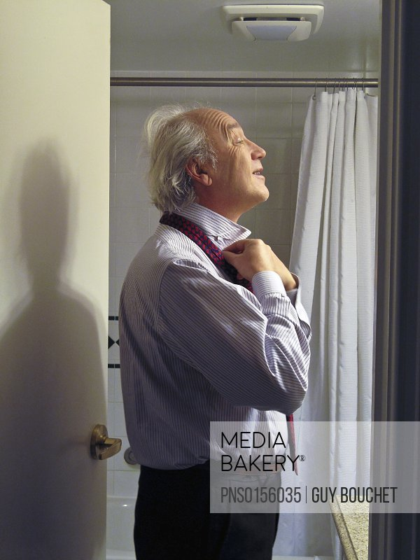 Man putting his necktie in a bathroom