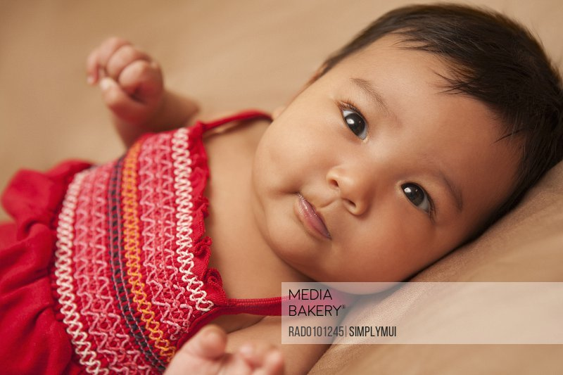 23d1ad102c2 Close-up portrait of Asian baby lying on back wearing red dress looking at  camera