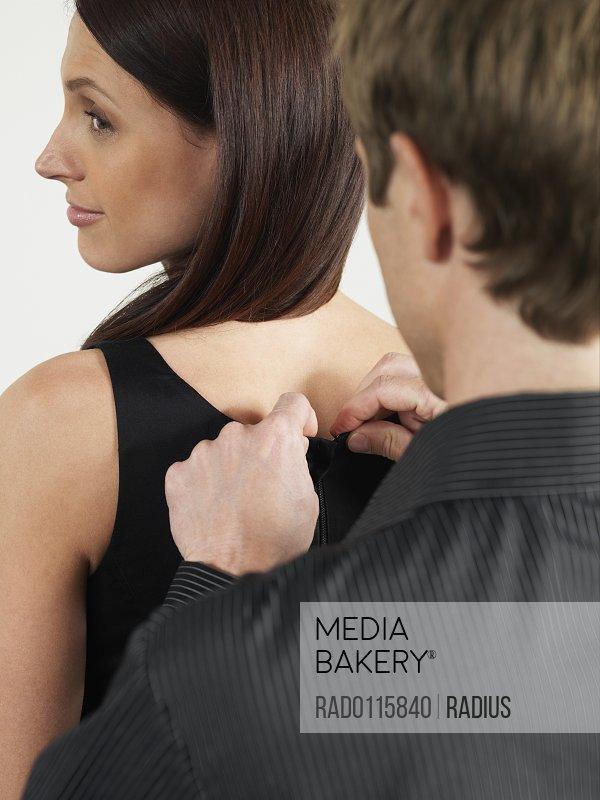 Man Zipping Woman's Dress
