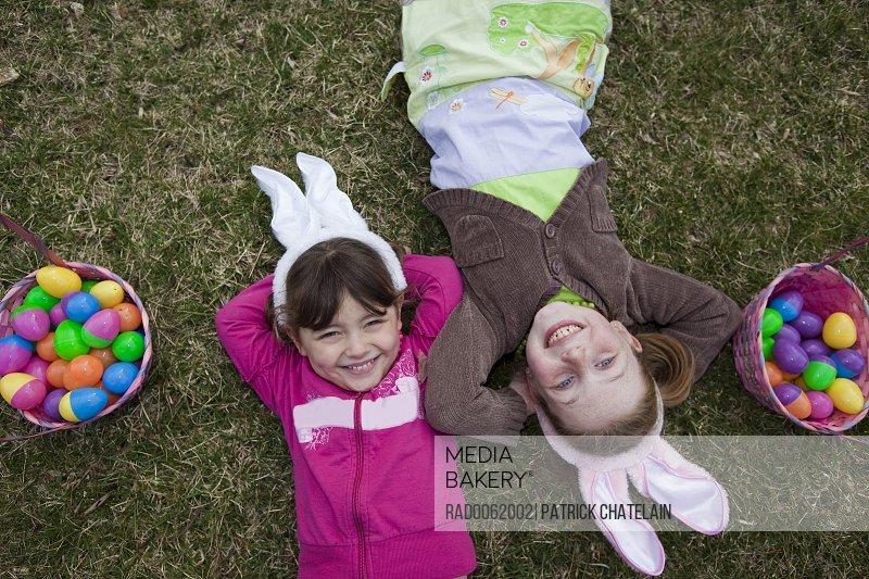Girls Lying Beside Easter Baskets