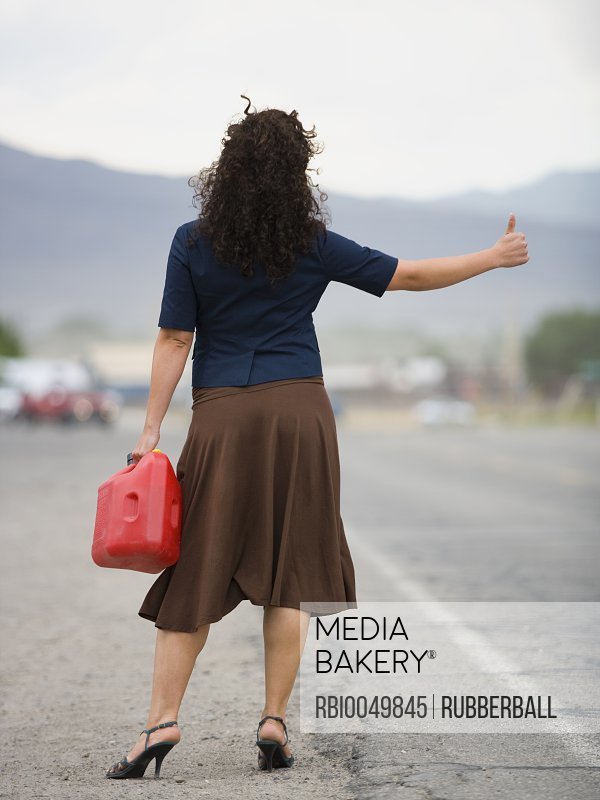 Rear view of a young woman holding a gas can and hitchhiking