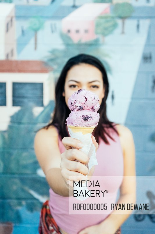 Young woman holding blueberry ice cream.