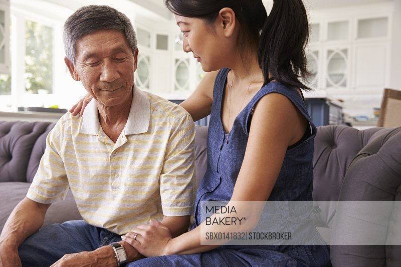 Adult Daughter Talking To Depressed Father At Home