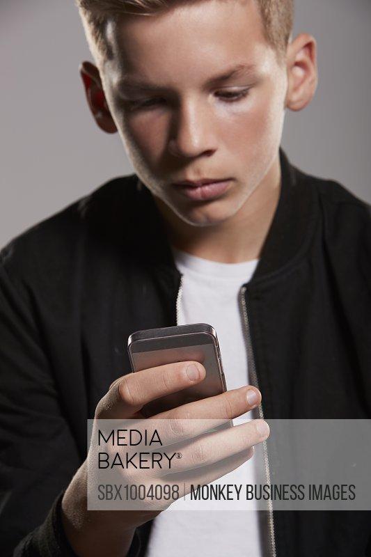 White teenage boy using mobile phone, waist up, vertical