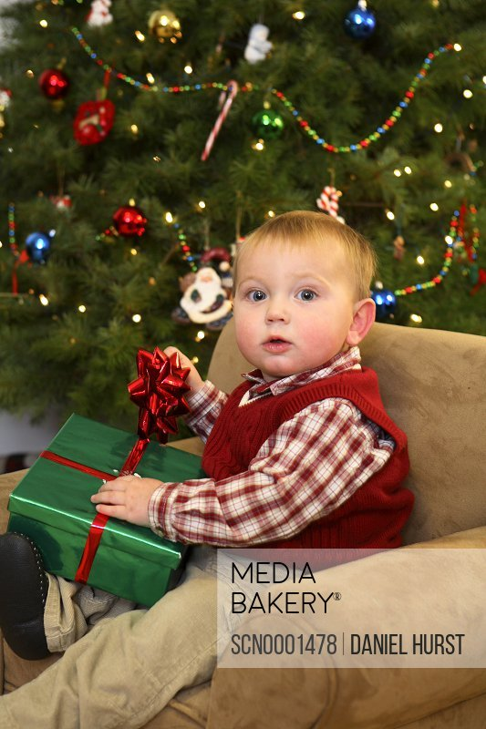 one year old boy opening christmas presents
