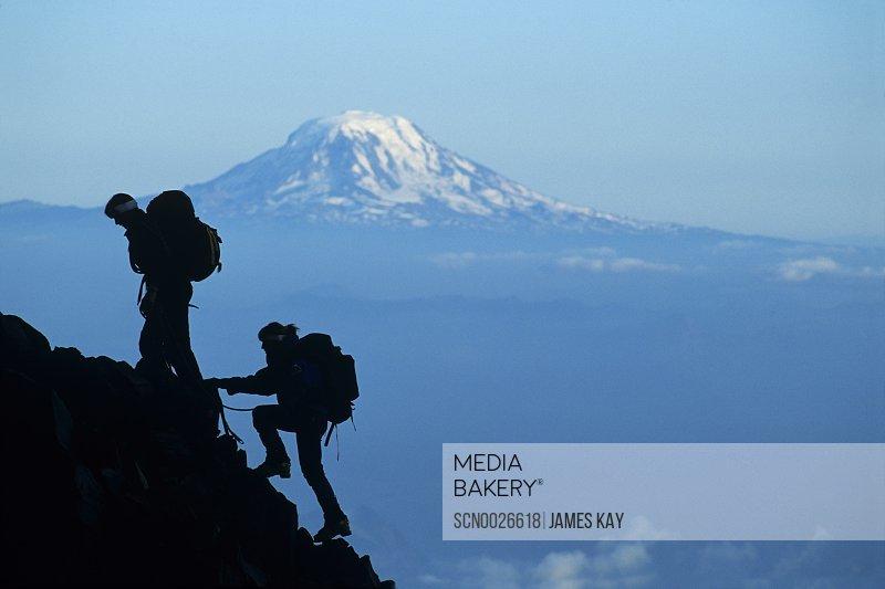Two climbers ascending Mount Rainier with Mount Adams on horizon, Mount Rainier National Park, Washington.