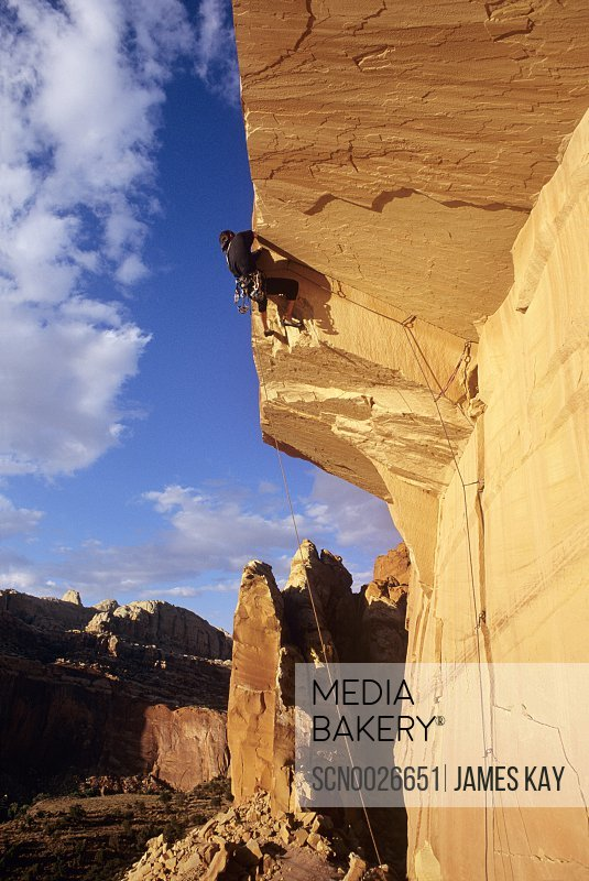 Rock climber pulls over Capitol Roof above Torrey in Capitol Reef National Park, Utah.