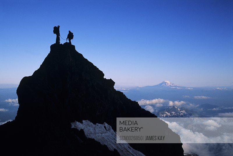 Two climbers atop spire at Camp Muir at the 10,000' level of Mount Rainer in Mount Rainier National Park,Washington. Mount Adams on the horizon.