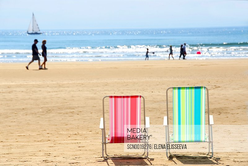 Two Empty Colorful Beach Chairs On A Sandy