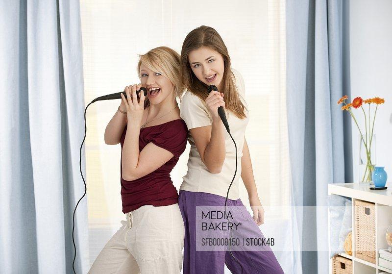 Two teenage girls singing in microphone