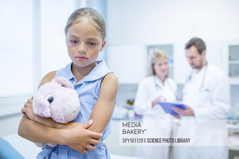 Sad girl in doctor's room hugging teddy