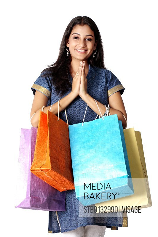 woman holding shopping bags and welcoming
