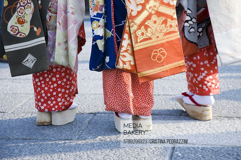 Geishas wearing traditional footwear and kimonos