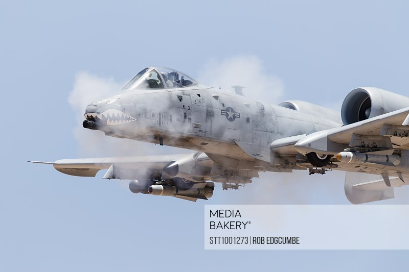 Photo by StockTrek Images - A U S  Air Force A-10 Thunderbolt II fires its  30mm gun at a strafe target