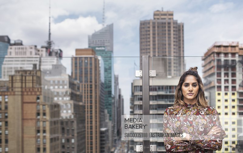 Front view of confident woman standing against glass window at rooftop restaurant