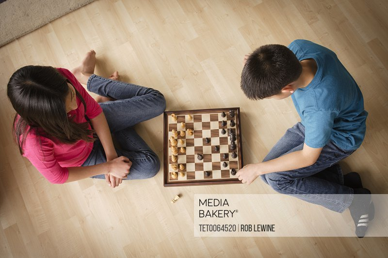 Siblings playing chess game