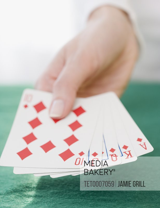 Woman holding straight flush playing cards