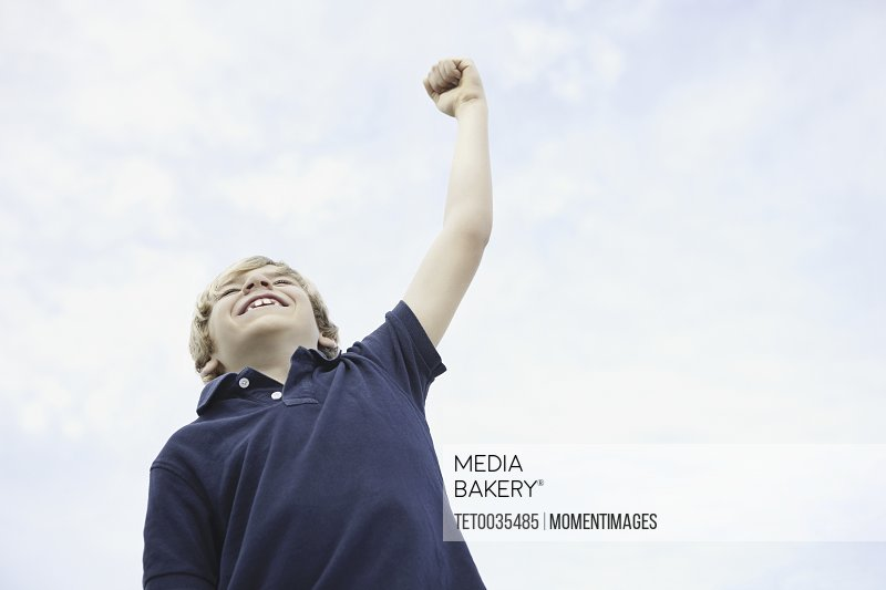 Young boy with his arm raised