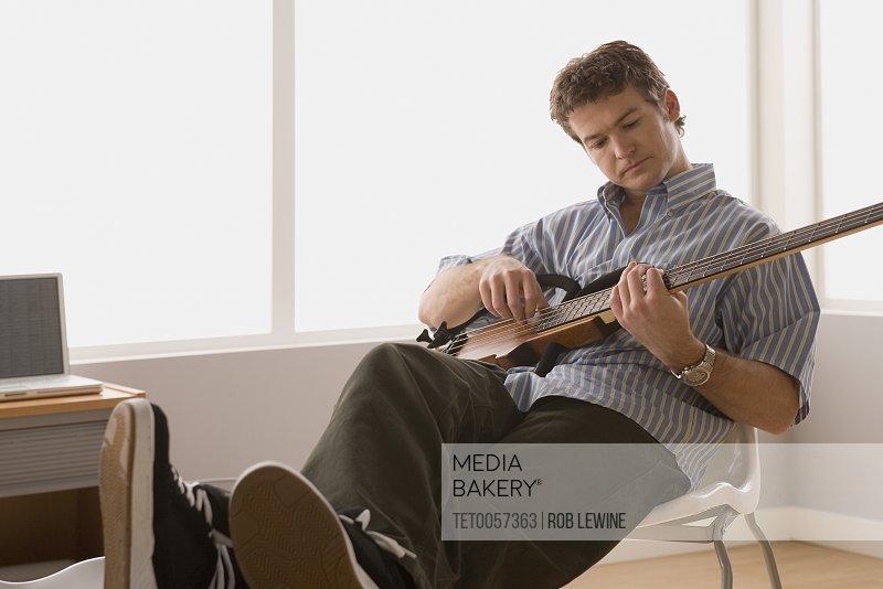 Young man playing electric base guitar