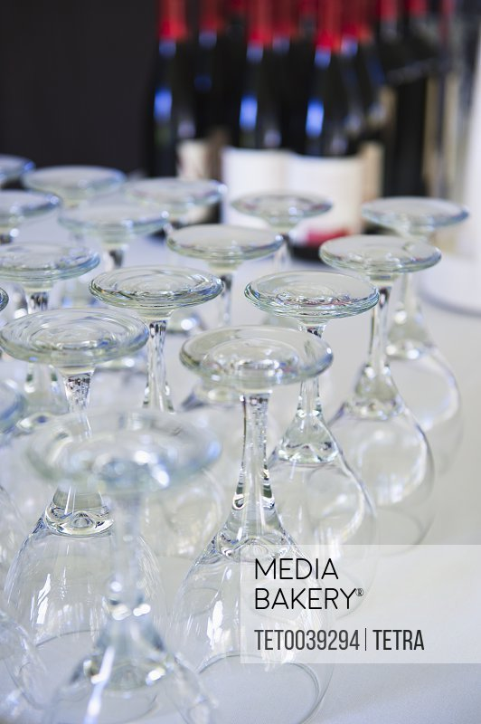 Wine glasses on table with bottles in background