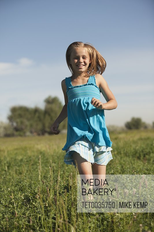 Young girl running in field
