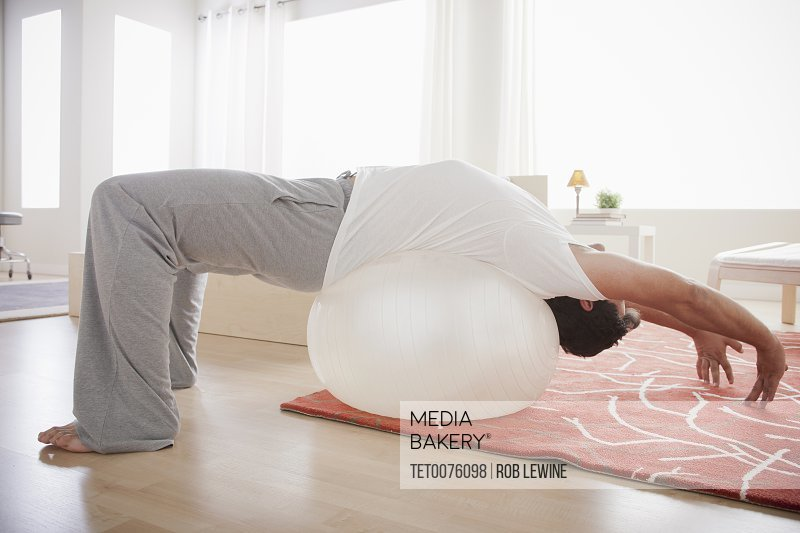 Mid adult men exercising with fitness ball