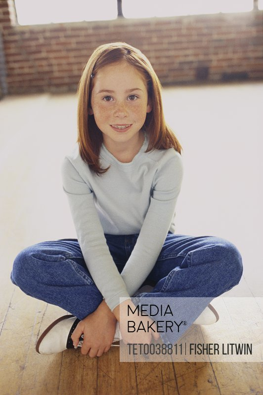Cute young girl sitting cross legged