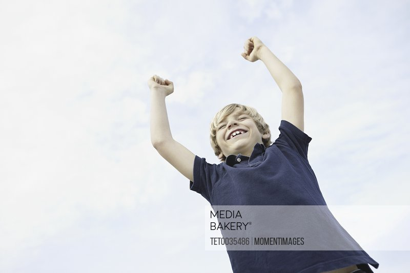 Happy young boy raising his arms in the air
