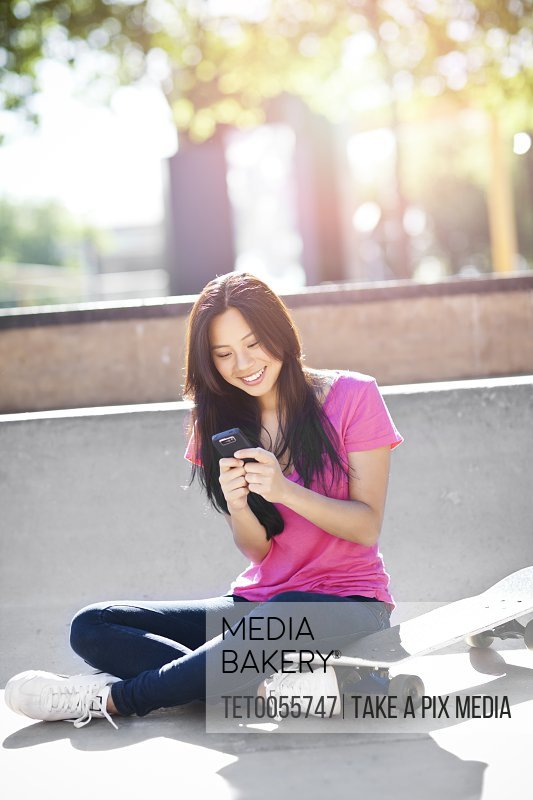 Young chinese woman text messaging while sitting on skateboard