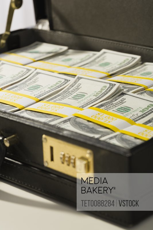 Photo by Tetra Images - Suitcase filled with US currency notes